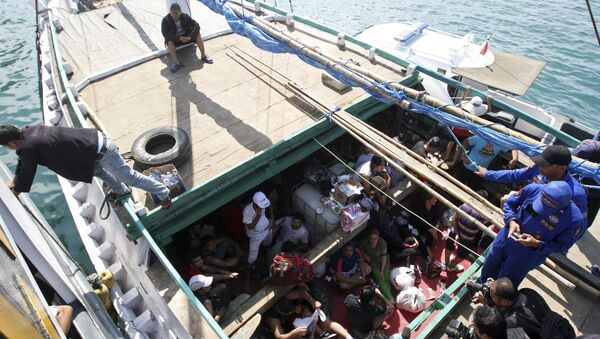 In this May 12, 2013 file photo, Iranian asylum seekers who were caught in Indonesian waters while sailing to Australia, sit on a boat, at Benoa port in Bali, Indonesia - Sputnik International
