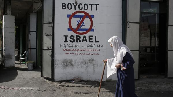 A Palestinian woman walks past a mural calling people to boycott Israeli goods in the al-Azzeh refugee camp near the West Bank city of Bethlehem on September 17, 2014 - Sputnik International