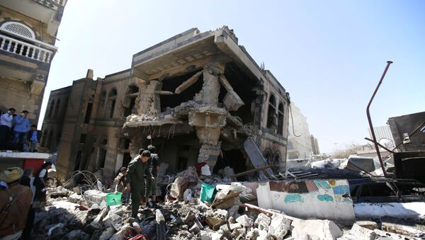 People inspect a house destroyed by Saudi-led airstrikes that killed a TV director, his wife, and three children in Sanaa, Yemen, Wednesday, Feb. 10, 2016 - Sputnik International