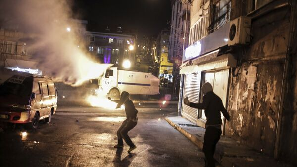 Protesters run after they threw a petrol bomb against a Turkish police water cannon during clashes in Istanbul, Sunday, Feb. 14, 2016, between police forces and people protesting against security operations against Kurdish rebels in southeastern Turkey - Sputnik International