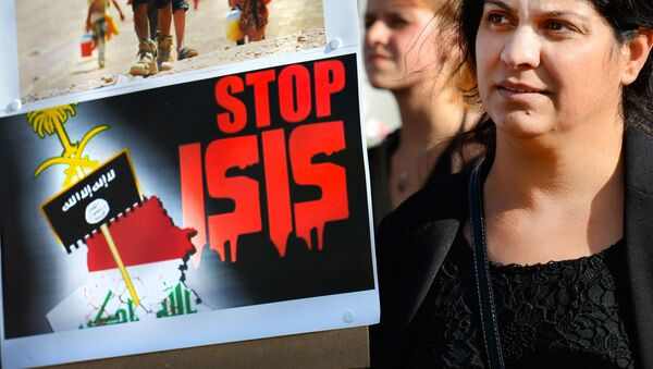 A holds a sign calling to Stop ISIS (ISIS fir Islamic State) on August 13, 2014 as she takes part in a demonstration called by Kurds in support of the Yezidis and the Christians in Iraq, in Arnhem, The Netherlands. - Sputnik International