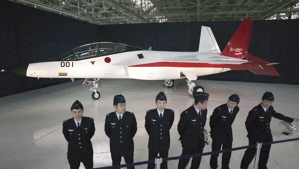 Defense Ministry officers stand in front of the first domestically-made stealth aircraft, X-2, at Nagoya Airport in Toyoyama town, central Japan, Thursday, Jan. 28, 2016. - Sputnik International