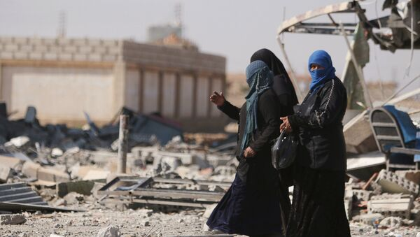 Women walk on rubble in al-Shadadi town, in Hasaka province, Syria February 26, 2016 - Sputnik International