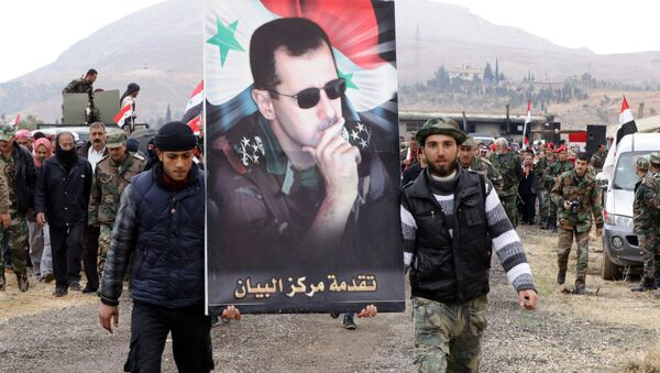 Syrian volunteers and their relatives wave the national flag and portraits of President Bashar al-Assad as they celebrate at the end of a paramilitary training conducted by the Syrian army in al-Qtaifeh, 50 kms north of the capital Damascus on February 22, 2016 - Sputnik International