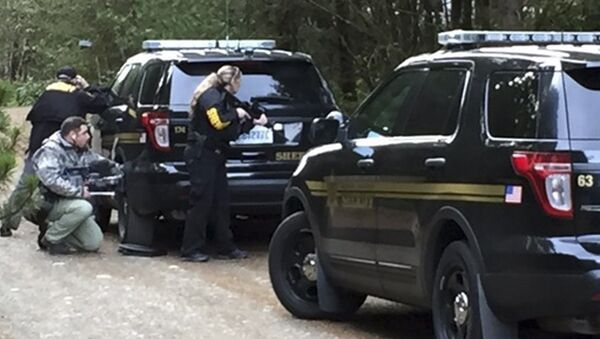 Police officers take cover behind vehicles lining the road during a standoff at a rural property near Belfair, Washington, February 26, 2016 - Sputnik International