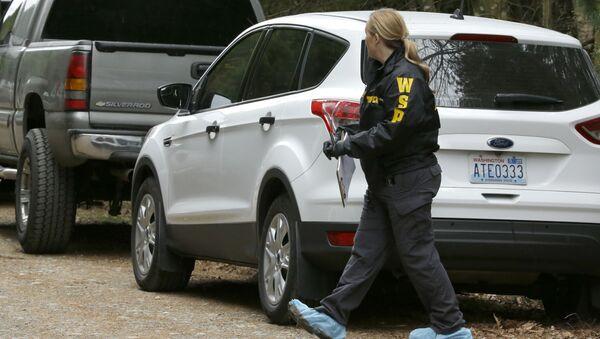 Washington State Patrol detective walks with protective foot covers on near the scene of a fatal shooting Friday, Feb. 26, 2016, near Belfair, Wash - Sputnik International