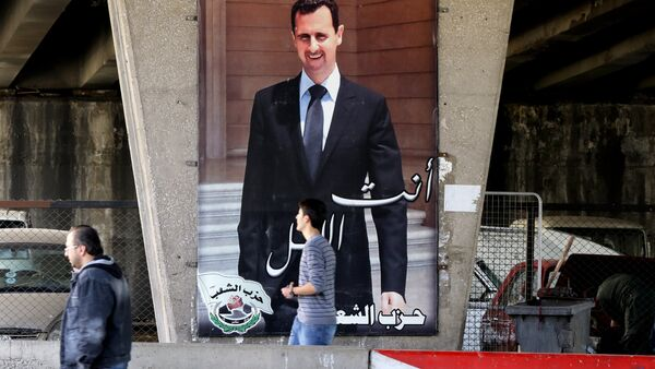 Syrian men walk past a poster bearing a portrait of President Bashar al-Assad in the capital Damascus, on February 27, 2016, as the first major ceasefire of the five-year war takes hold and an international task force prepares to begin monitoring the landmark truce - Sputnik International