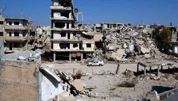 In this picture taken Friday, Feb. 26, 2016, a car drives through a devastated part of the old city of Homs, Syria - Sputnik International