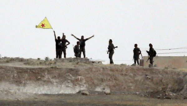 In this Monday, June 15, 2015 file photo taken from the Turkish side of the border between Turkey and Syria, in Akcakale, southeastern Turkey, Kurdish fighters with the Kurdish People's Protection Units, or YPG, wave their yellow triangular flag in the outskirts of Tal Abyad, Syria - Sputnik International