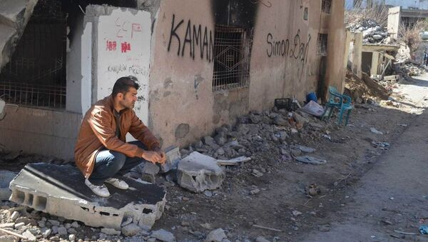 A resident of Cizre sits next to his ruined and burned house. - Sputnik International