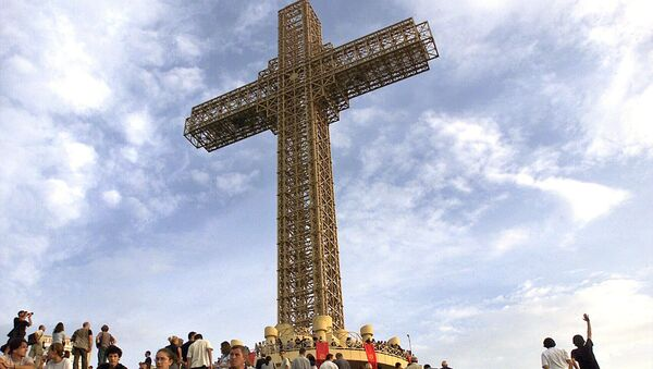 Macedonian Orthodox believers sit around a massive metal cross during its sanctification ceremony on top of Mt. Vodno, just above Macedonia's capital Skopje, on Wednesday, Aug. 28, 2002 - Sputnik International