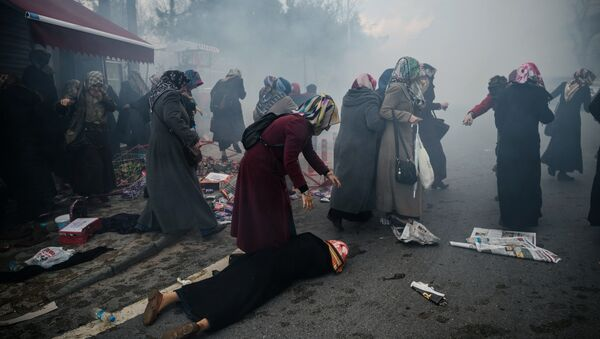 Women helps another woman who felt as Turkish anti-riot police officers launch tear gas to disperse supporters in front of the headquarters of the Turkish daily newspaper Zaman in Istanbul on March 5, 2016, after Turkish authorities seized the headquarters in a midnight raid - Sputnik International