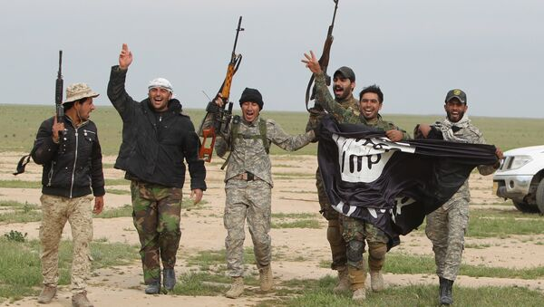 Iraqi Shiite fighters from the Popular Mobilisation units carry an Islamic State (IS) group flag on March 3, 2016, during an operation in the desert of Samarra aimed at retaking areas from IS jihadists - Sputnik International