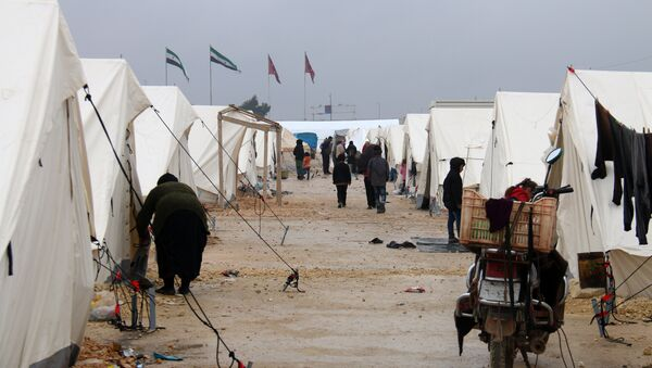 Displaced Syrians fleeing areas in the northern embattled province of Aleppo, walk past tents at the Bab al-Salama camp, set up outside the Syrian city of Azaz on Syria's northern border with Turkey on February 12, 2016 - Sputnik International