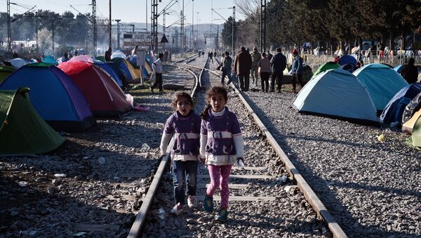 Sisters walk on railway tracks where refugees installed their tents at the makeshift camp of the Greek-Macedonian border near the Greek village of Idomeni, on March 5, 2016, where thousands of refugees and migrants wait to cross the border into Macedonia - Sputnik International