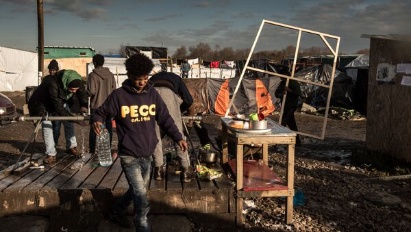 Men wash up at a water source at the migrant camp known as the Jungle in Calais on December 7, 2015 - Sputnik International