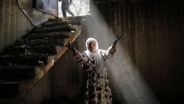 A woman reacts while walking among the ruins of damaged buildings following heavy fighting between government troops and Kurdish fighters, on March 2, 2016 in the southeastern Turkey Kurdish town of Cizre, near the border with Syria and Iraq - Sputnik International