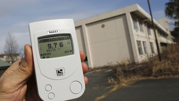 Reuters reporter measures a radiation level of 9.76 microsieverts per hour in front of Kumamachi Elementary School inside the exclusion zone in Okuma, near Tokyo Electric Power Co's (TEPCO) tsunami-crippled Fukushima Daiichi nuclear power plant, Fukushima Prefecture, Japan, February 13, 2016 - Sputnik International