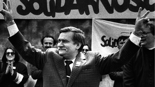 Polish President and Solidarity founding leader Lech Walesa shows v-sign in front of Solidarity poster during his presidential campaign in Plock in this May 7, 1989 file photo - Sputnik International