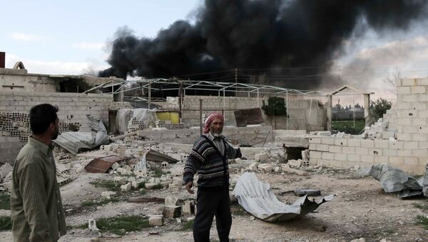 A Syrian man stands in the courtyard of his farm as smoke billows in the background following reported air strikes near the rebel-held village of al-Chifouniya, on the outskirts of the capital Damascus, on March 4, 2016 - Sputnik International