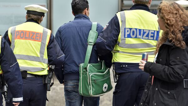 Police lead away a man at the main train station Tuesday, Jan. 12, 2016, in Cologne, Germany - Sputnik International
