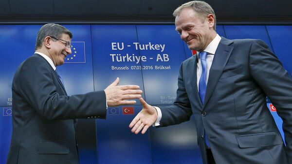 Turkish Prime Minister Ahmet Davutoglu (L) shakes hands with European Council President Donald Tusk after a news conference at the end of a EU-Turkey summit in Brussels March 8, 2016. - Sputnik International