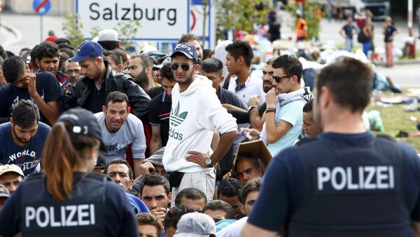 German police officers standing in front of migrants waiting to cross the border from Austria to Germany near Freilassing, Germany September 17, 2015. - Sputnik International