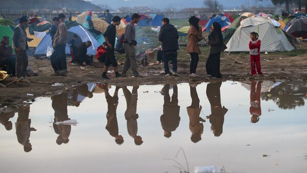 Migrants are reflected in a puddle at the northern Greek border station of Idomeni, Tuesday, March 8, 2016. - Sputnik International