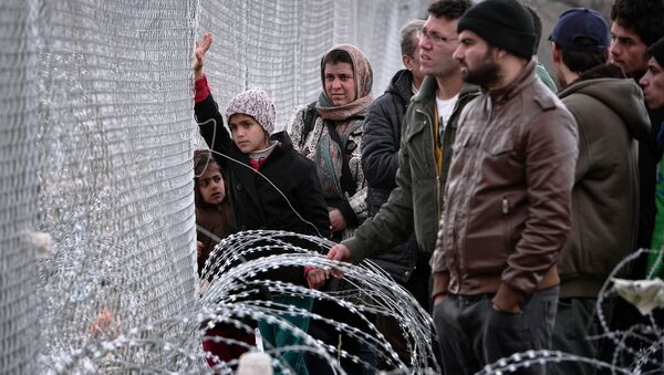People look at the Macedonian side of the border through a fence in the makeshift camp at the Greek-Macedonian border near the Greek village of Idomeni, on March 3, 2016. - Sputnik International
