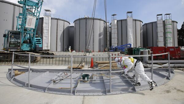 Men wearing protective suits and masks work in front of welding storage tanks for radioactive water, under construction in the J1 area at the Tokyo Electric Power Co's (TEPCO) tsunami-crippled Fukushima Daiichi nuclear power plant in Okuma in Fukushima prefecture. (File) - Sputnik International