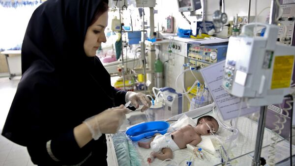 In this Monday, Dec. 30, 2013 photo, a nurse cares for a newborn baby in the Neonatal Intensive Care Unit of the Mofid Children Hospital in Tehran, Iran - Sputnik International