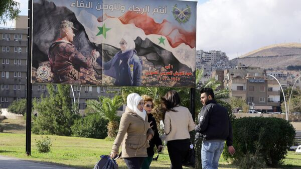 Syrians walk past a billboard bearing a national flag and a slogan which reads in Arabic You are the future and long live the country in Damascus on December 2, 2015 - Sputnik International