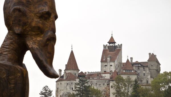 A sculpture commemorating Petru Darascu, a Romanian priest who survived several Communist prisons, by Ovidiu Nicolae Popa is backdropped by the Gothic Bran Castle, better known as Dracula Castle, in Bran, in Romania's central Transylvania region, Saturday, Oct. 8, 2011 - Sputnik International