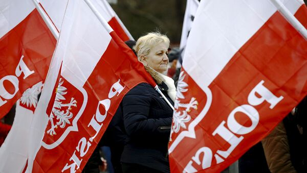 A woman holds the Polish national flag as she takes part in a march demanding their government to respect the country's constitution in Warsaw, Poland, March 12, 2016. - Sputnik International