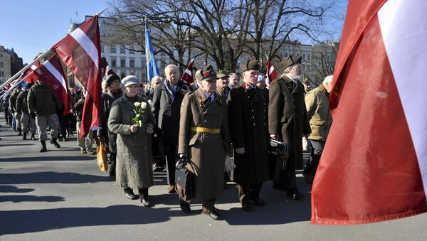 People carry flowers and Latvian flags as they march to the Freedom Monument to commemorate World War II veterans who fought in Waffen SS divisions, in Riga, Latvia, Monday, March 16, 2015 - Sputnik International