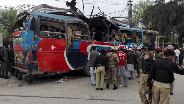 Policemen and rescue officials walk near a bus damaged in a bomb blast in Peshawar, Pakistan March 16, 2016 - Sputnik International