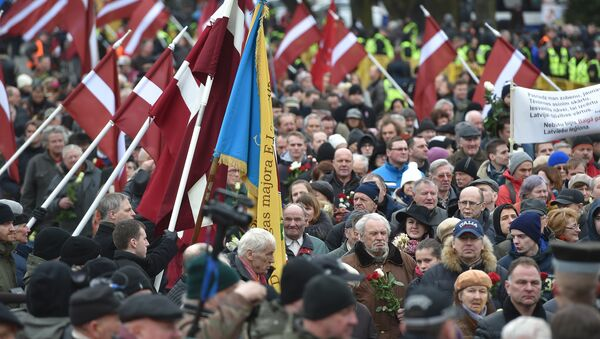 Veterans of the Latvian Legion, a force that was commanded by the German Nazi Waffen SS during WWII, and their sympathizers carry flowers as they walk to the Monument of Freedom in Riga, Latvia on March 16, 2016 - Sputnik International