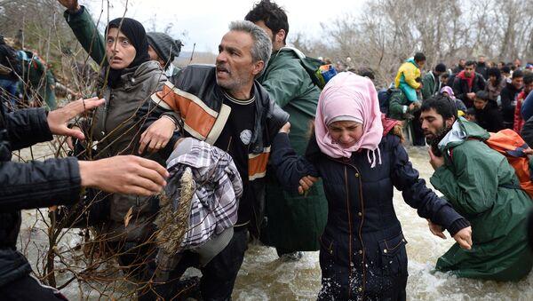 Беженцы и мигранты пересекают реку по пути в Македонию из импровизированного лагеря на греко-македонской границе - Sputnik International