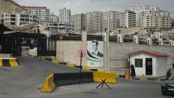 A portrait of Syrian President Bashar Assad is mounted on a wall in Damascus, Syria, Thursday, March 3, 2016. - Sputnik International