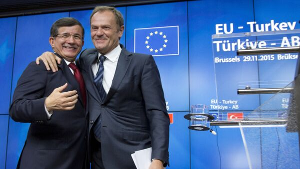 European Council President Donald Tusk, right, puts his arm on the shoulder of Turkish Prime Minister Ahmet Davutoglu after a media conference at an EU-Turkey summit in Brussels on Sunday, Nov. 29, 2015. - Sputnik International