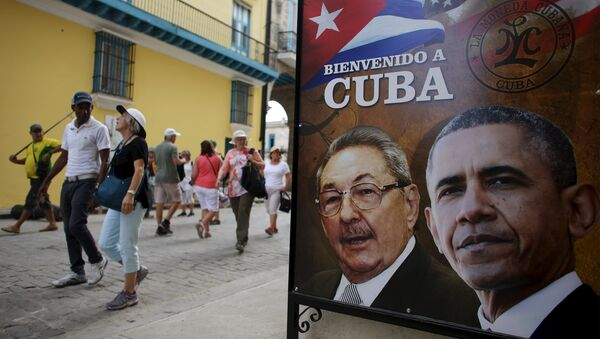 Tourists pass by images of US President Barack Obama and Cuban President Raul Castro in a banner that reads Welcome to Cuba at the entrance of a restaurant in downtown Havana, March 17, 2016. - Sputnik International