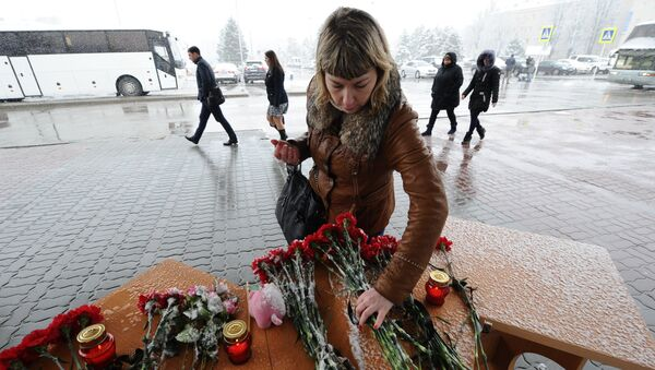 A woman lays flowers at Rostov-on-Don airport where the Boeing-737-800 passenger jet crashed on landing. - Sputnik International