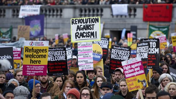 Demonstrators hold banners in support of refugees as they march through central London on March 19, 2016. - Sputnik International