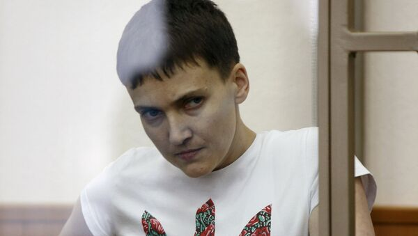 Former Ukrainian army pilot Nadezhda Savchenko looks out from a glass-walled cage as she attends a court hearing in the southern border town of Donetsk in Rostov region, Russia, in this file picture taken March 9, 2016 - Sputnik International