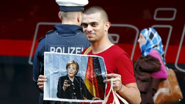 A migrant holds a picture of German Chancellor Angela Merkel after arriving to the main railway station in Munich, Germany, in this September 5, 2015. - Sputnik International