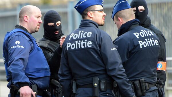 Policemen speak at a security perimeter near Maalbeek metro station, on March 22, 2016 in Brussels, after a blast at this station near the EU institutions caused deaths and injuries - Sputnik International