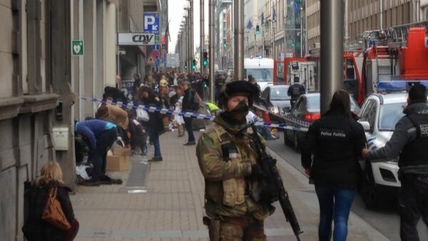 In this image taken from TV an armed member of the security forces stands guard as emergency services attend the scene after a explosion in a main metro station in Brussels on Tuesday, March 22, 2016 - Sputnik International
