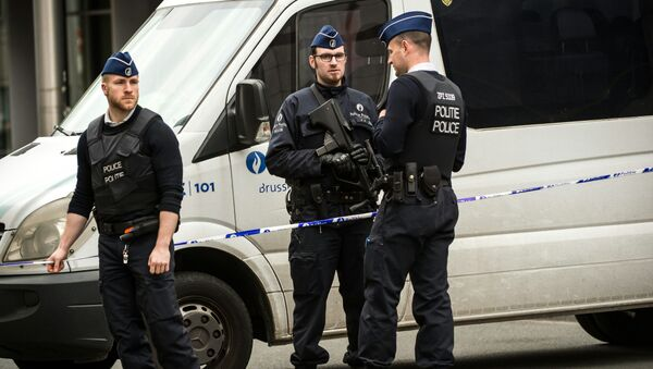 Policemen stand guard at the entrance of a security perimeter set in the Rue de la Loi near the Maalbeek subway station, in Brussels, on March 22, 2016 - Sputnik International