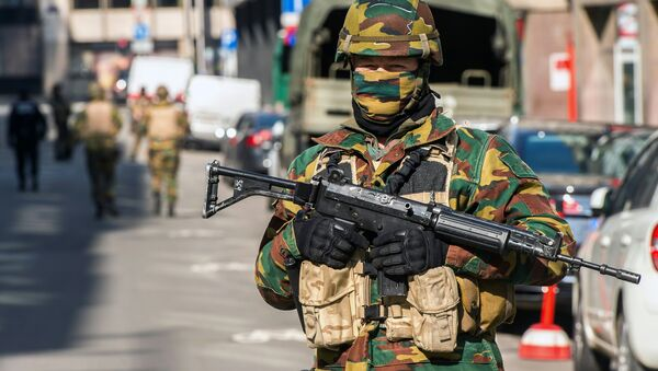 A soldier blocks the access to roads close to the Maalbeek metro station in Brussels on March 22, 2016 after a series of apparently coordinated explosions ripped through Brussels airport and a metro train, killing at least 14 people in the airport and 20 people in the metro in the latest attacks to target Europe - Sputnik International
