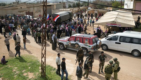People gather around a Russian military truck to receive a food aid in Maarzaf, about 15 kilometers west of Hama, Syria, Wednesday, March 2, 2016 - Sputnik International
